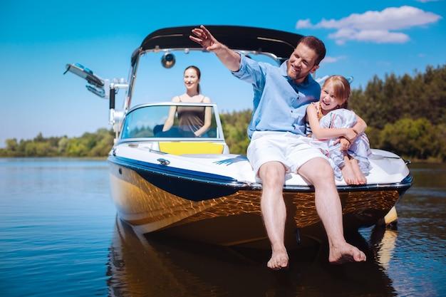 Storie interessanti. allegro giovane padre che indica le rive del fiume e racconta le storie della sua piccola figlia mentre sono seduti sulla prua della barca