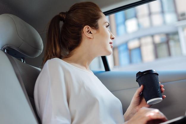 Vista interessante. bella donna piacevole positiva seduta in macchina e guardando fuori dalla finestra mentre si gode la vista
