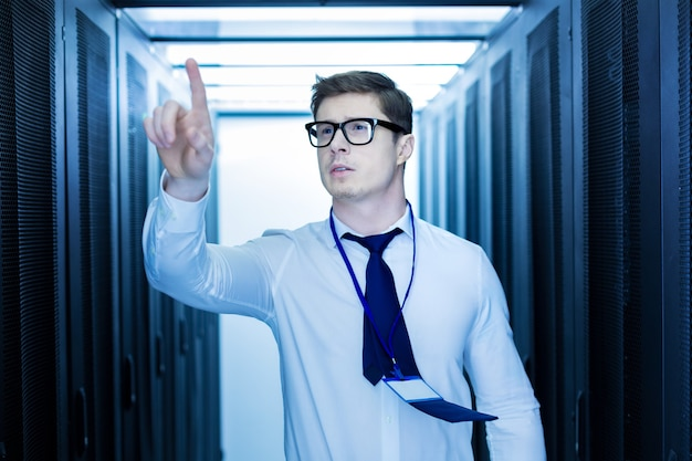 Lavoro interessante. bell'uomo ispirato che lavora in un data center e indica con il dito