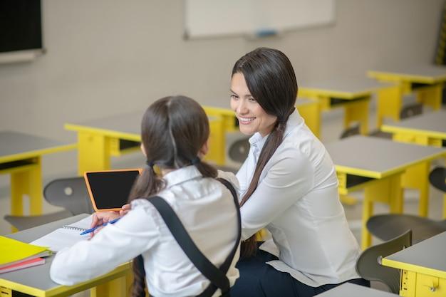 È interessante notare che il giovane insegnante sorridente con tablet e attenta studentessa seduto accanto a
