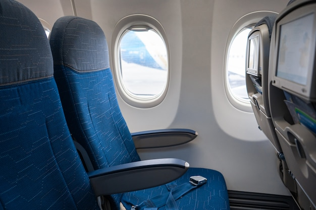 L'interno del velivolo. cabina dell'aeroplano vuota. file di sedili passeggeri con schermi nei poggiatesta