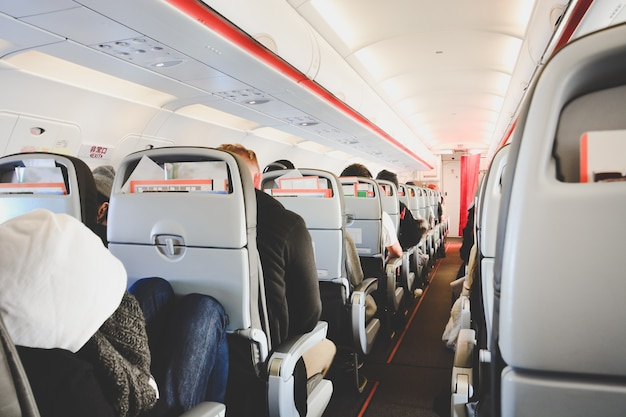 Interno di un aereo in classe economica con passeggeri seduti su sedili compagnia aerea low cost