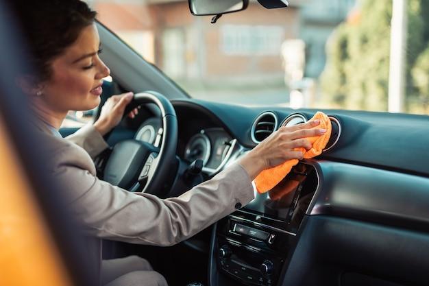 Dettagli interni dell'auto. felice imprenditrice pulisce e pulisce l'interno della sua auto.