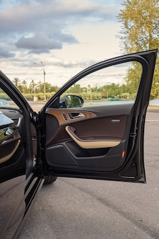 L'interno dell'auto è nero, il sedile del conducente è in pelle marrone e beige.