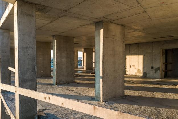 Interno di una stanza di condominio residenziale in cemento con pareti nude non finite e pilastri di supporto per futuri muri in costruzione.