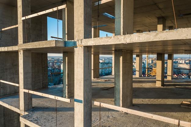 Interno di una stanza di edificio di appartamenti residenziali in cemento con pareti nude non finite e pilastri di supporto