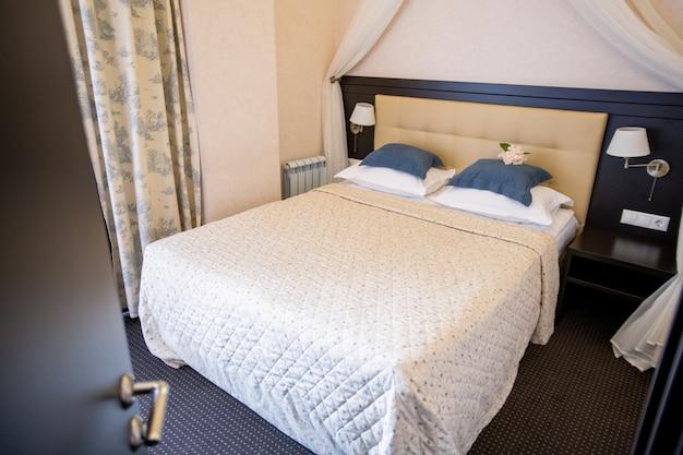 Interno della camera d'albergo accogliente contemporanea con letto matrimoniale, due lampade su entrambi i lati e comodino in legno