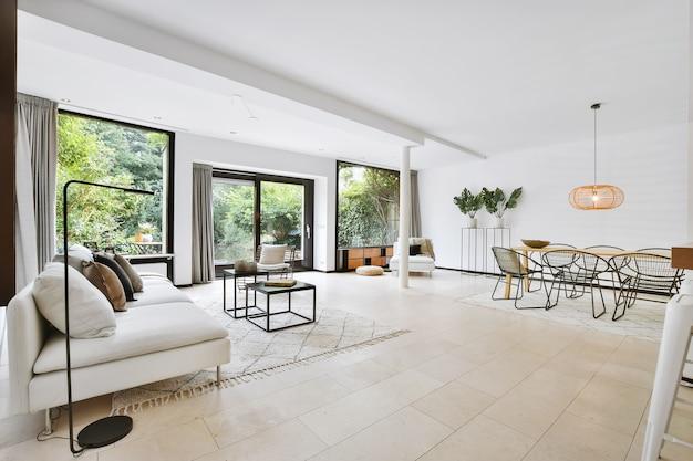Interno del soggiorno contemporaneo con divano con morbidi cuscini e lampada da terra in piano