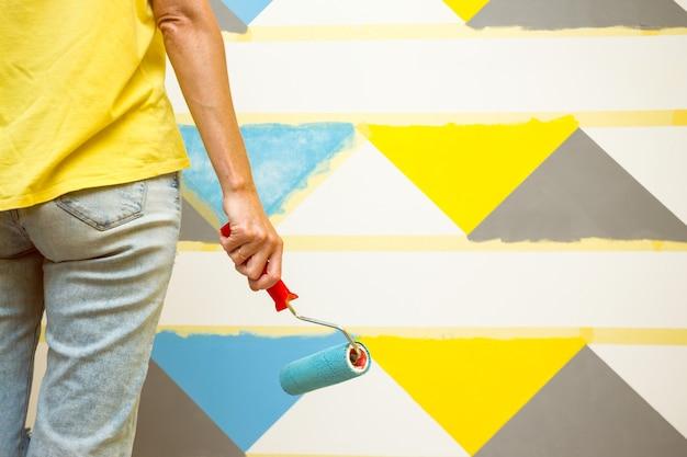 Interior design. la ragazza dipinge il muro in un motivo geometrico.