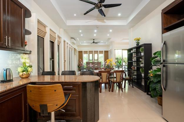 Il design degli interni di casa, casa, villa e appartamento dispone di frigorifero, sgabello, bancone della cucina, ventilatore a soffitto, mensola e tavolo da pranzo