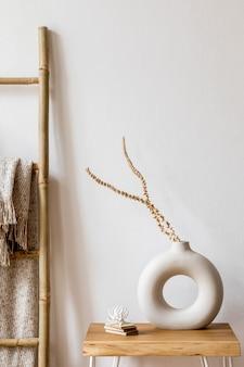 Interior design del soggiorno con eleganti fiori secchi in vaso, scala in legno, plaid e accessori personali nell'arredamento moderno della casa.