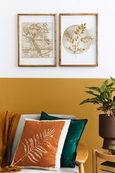 Interior design del soggiorno moderno con due cornici per poster mock up, divano elegante, pianta, cuscino e accessori personali in un'elegante messa in scena domestica. giallo miele concetto.