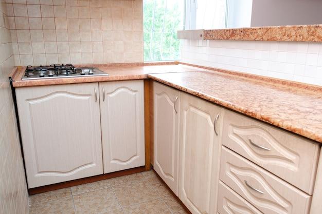Il design degli interni di una moderna cucina compatta intelligente e stretta con mobili contemporanei bianchi, piastrelle in ceramica beige sul muro, fornello a gas e vista della finestra.