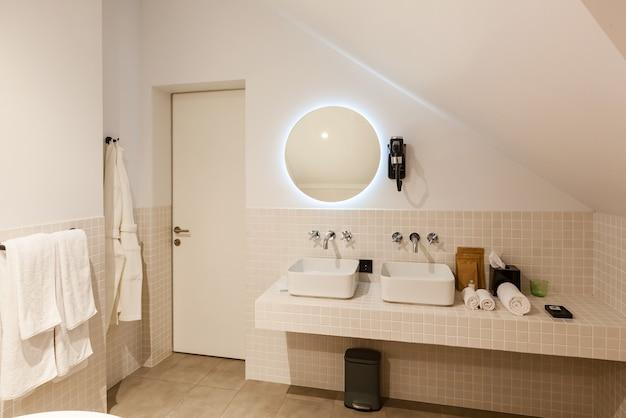 Interni e design della moderna toilette e bagno, articoli per il bagno asciugacapelli, specchio, accappatoio, vasca da bagno, lavabo, rubinetti dell'acqua