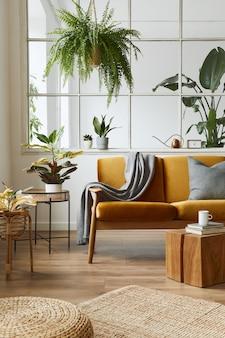 Interior design di open space scandinavo con divano in velluto giallo, piante, mobili, libri, cubi di legno e accessori personali in un'elegante messa in scena domestica. modello.