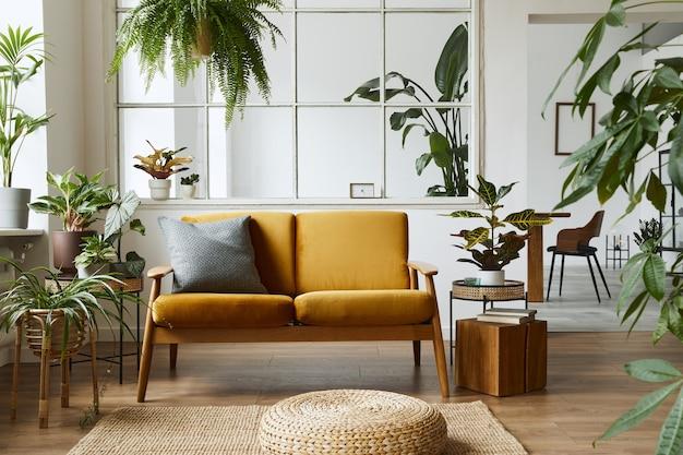 Interior design di open space scandinavo con divano in velluto giallo, piante, mobili, libri, cubi di legno e accessori personali in un elegante allestimento domestico.