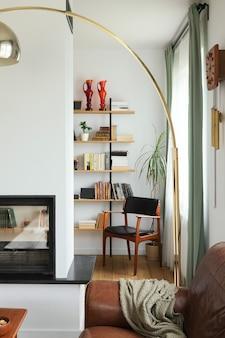 Interior design di interni eleganti del soggiorno con mobili vintage, biblioteca per l'home office, camino, lampada, decorazione ed eleganti accessori personali nell'arredamento della casa. modello.