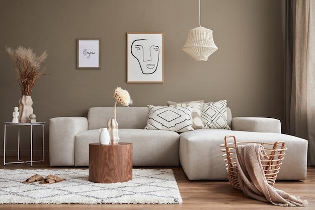 Interior design di un elegante soggiorno con divano moderno neutro, fattorie di poster, fiori secchi in vaso, tavolini da caffè, decorazioni ed eleganti accessori personali nell'arredamento della casa.