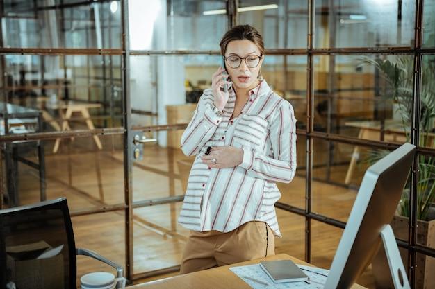 Arredatore d'interni. designer di interni professionista incinta che lavora dal suo ufficio spazioso e luminoso