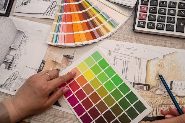 La mano dell'arredatore d'interni seleziona un colore dalla tavolozza. concetto di ristrutturazione Foto Premium
