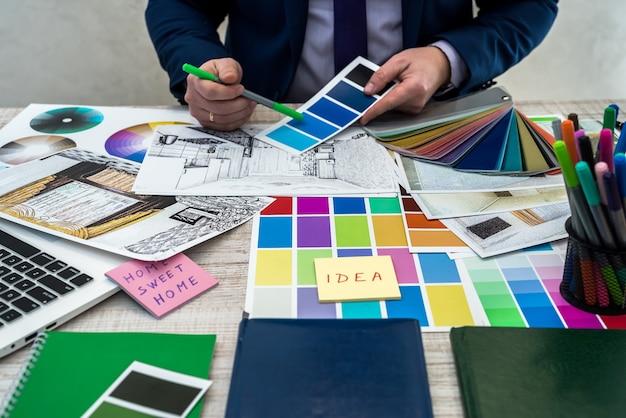 La mano dell'interior designer che lavora con lo schizzo dell'illustrazione, la combinazione di colori del materiale, il taccuino e il materiale. concetto di ristrutturazione, riparazione o decorazione della casa