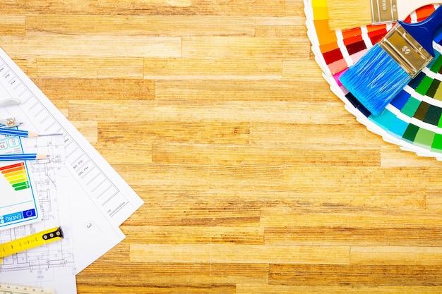 Tavolo da lavoro di interior designer con pianta architettonica della casa, tavolozza colori e pennelli