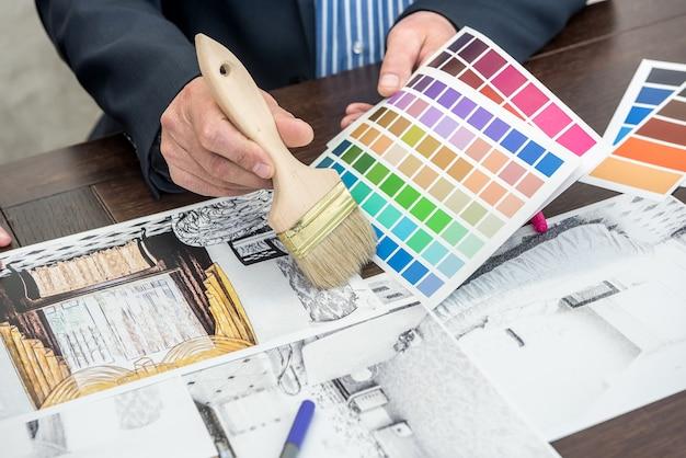 Il designer di interni lavora con lo schizzo dell'appartamento, la tavolozza dei colori, il laptop alla scrivania dell'ufficio. progetto progetto casa