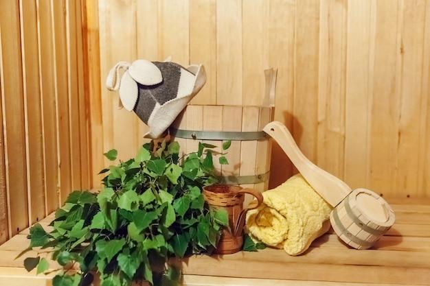 Dettagli interni sauna finlandese bagno di vapore con accessori sauna tradizionale bacino scopa di betulla scoop cappello in feltro asciugamano. vecchio concetto russo tradizionale della stazione termale dello stabilimento balneare. rilassa il concetto di bagno del villaggio di campagna