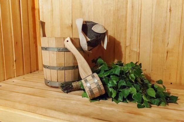 Dettagli interni sauna finlandese bagno di vapore con accessori sauna tradizionale bacino scopa scopa scoop cappello in feltro. vecchio concetto russo tradizionale della stazione termale dello stabilimento balneare. rilassa il concetto di bagno del villaggio di campagna