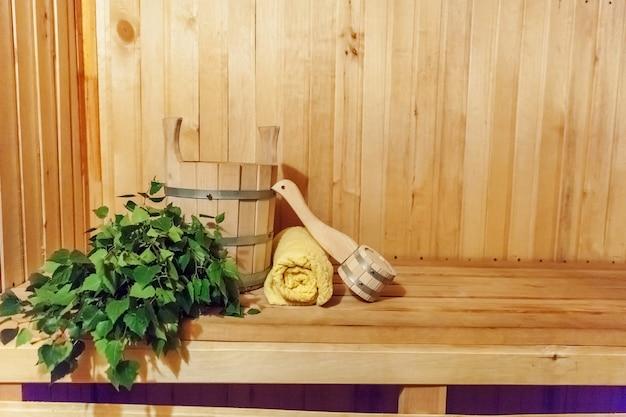Dettagli interni sauna finlandese bagno di vapore con accessori per sauna tradizionale bacino di betulla scopa asciugamano paletta. vecchio concetto russo tradizionale della stazione termale dello stabilimento balneare. rilassa il concetto di bagno del villaggio di campagna