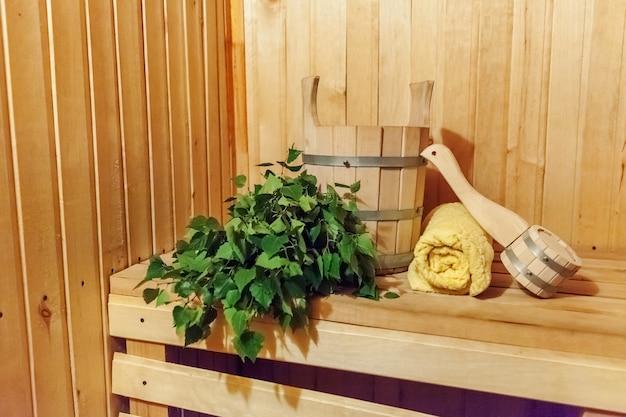 Dettagli interni sauna finlandese bagno di vapore con accessori per sauna tradizionale bacino di betulla scopa asciugamano paletta. vecchio concetto russo tradizionale della stazione termale dello stabilimento balneare. rilassa il concetto di bagno del villaggio di campagna Foto Premium
