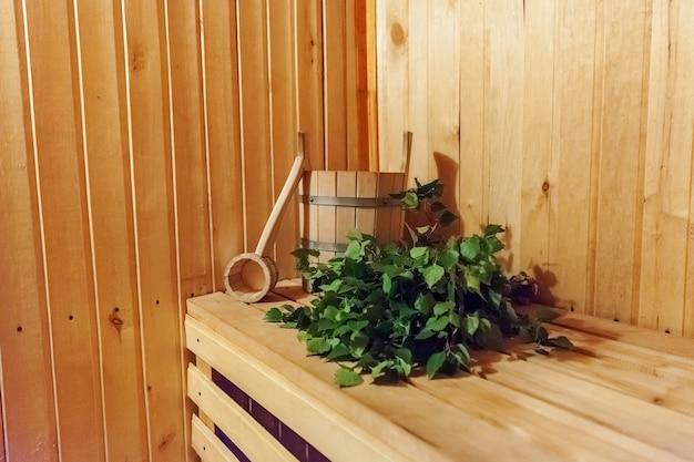 Dettagli interni sauna finlandese bagno di vapore con accessori per sauna tradizionale, paletta per scopa in betulla. vecchio concetto russo tradizionale della stazione termale dello stabilimento balneare. rilassa il concetto di bagno del villaggio di campagna