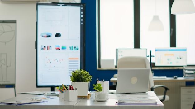 Interno di un ufficio creativo vuoto, nuova attività finanziaria, avviare una società senza persone al suo interno. azienda dal design moderno e tavolo da conferenza pronto per il brainstorming senza nessuno in camera
