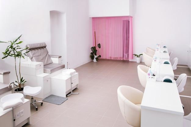 Interno del salone per unghie moderno vuoto. posti di lavoro per maestri di manicure