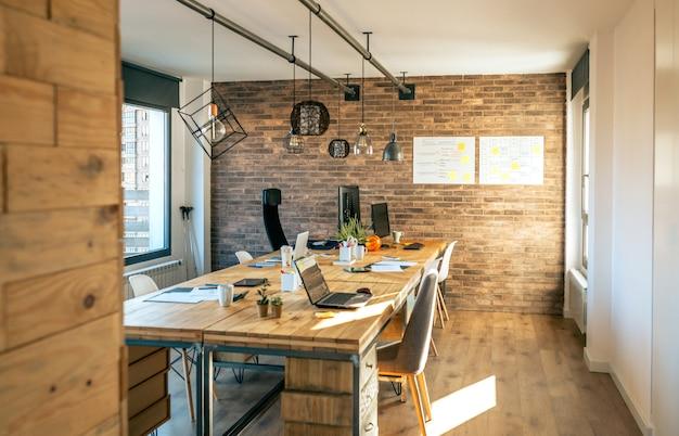 Interno di un ufficio di coworking in stile industriale con vari luoghi di lavoro