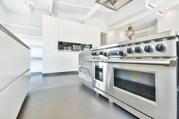 Interno della cucina con moderne stufe in acciaio inox in appartamento progettato in stile minimal