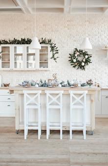 Cucina leggera interna con la decorazione e l'albero di natale. cucina bianca in stile classico. natale in cucina. cucina luminosa in tonalità bianche con il natale.