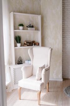 Interno del soggiorno con comoda poltrona beige sullo scaffale di fondo con libri, fiori e piante. contemporaneo della camera da letto accogliente bianca. design urbano moderno della stanza.