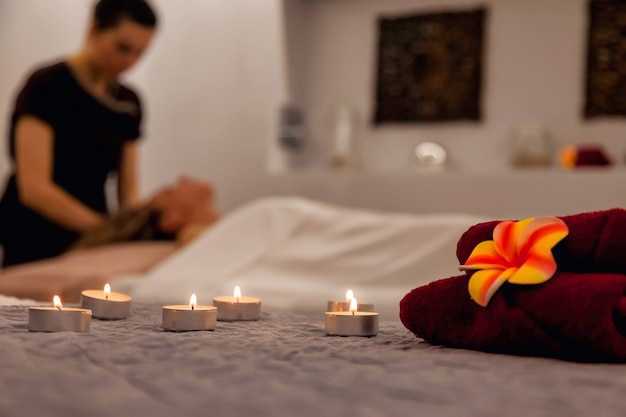 Interno del salone spa di lusso con candele e massaggiatore facendo trattamenti al cliente in background. pubblicità grandi sfondi per salone di bellezza. concetto di salute, giovinezza e bellezza. copia spazio