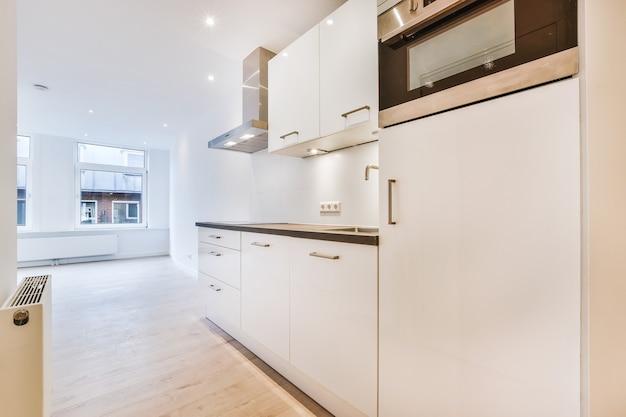 Interno della cucina moderna con mobili bianchi e nuovi elettrodomestici in appartamento in stile minimal