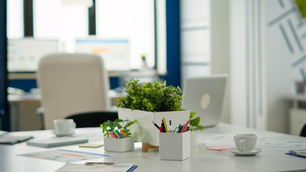 Interno del moderno ufficio finanziario a pianta aperta senza persone, interni eleganti con tavolo e sedie per riunioni. centro affari con area di brainstorming, inquadratura di una stanza vuota con mobili moderni.