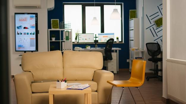 Interno di un moderno ufficio open space senza persone, interni eleganti con tavolo, divano e sedie. area di sosta nel centro affari con un piccolo divano, inquadratura di una stanza vuota con mobili moderni.
