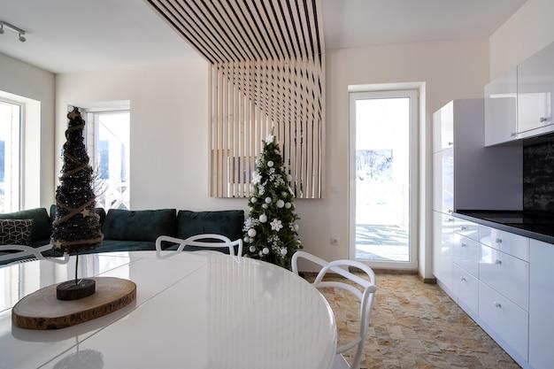 Interno della moderna cucina spaziosa con pareti bianche, elementi decorativi in legno, mobili contemporanei e grande divano morbido.