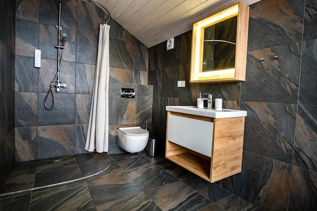 Interno del bagno moderno ed elegante con pareti piastrellate nere, posto doccia tenda e mobili in legno con lavabo e grande specchio illuminato.