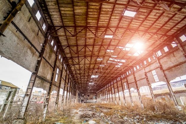 Interno del vecchio capannone distrutto con buchi nel tetto e nelle pareti.