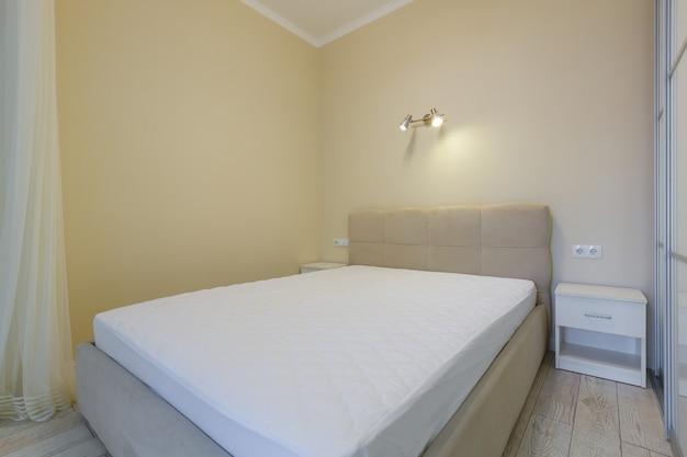 Foto interna di una grande camera da letto con un letto grande e un armadio