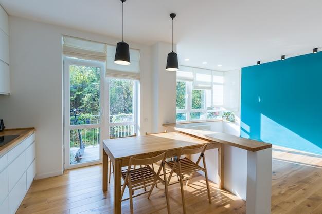 Foto di interni di una cucina studio, in bianco con grandi finestre