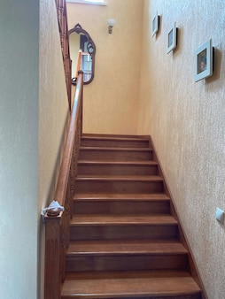 Foto interna di una scala in legno di una casa privata in stile vintage nei toni del beige con uno specchio nella campata. concetto di costruzione e architettura.