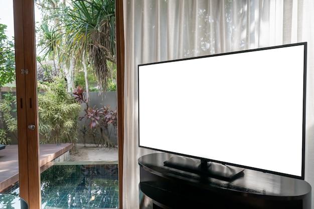 Interno della stanza, grande finestra con tenda bianca vista piscina, schermo bianco tv mock up sul tavolo.