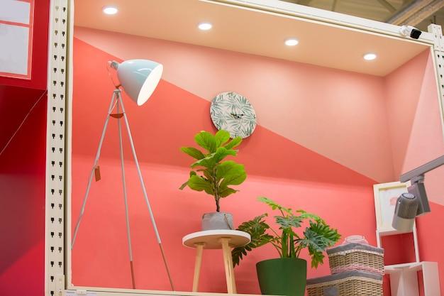 Interno di una stanza nella vetrina di un negozio. lampada da tavolo con piante e cesti sullo sfondo di una parete rosa. concetto di arredo dell'appartamento.